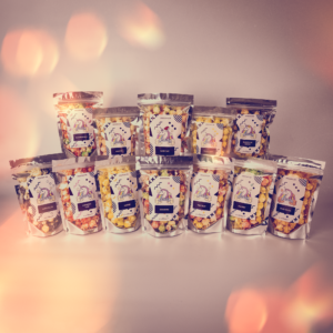 All 12 Popcorn pouches that come in the popcorn advent calender showing a range of different coloured popcorn.