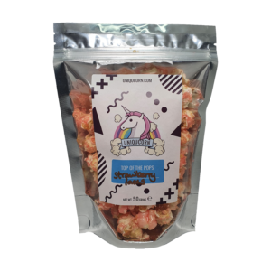 A pouch of Red gourmet popcornwith a white patterned sticker with a Unicorn on the Logo. Strawberry Laces is hand written for the flavour