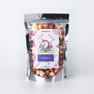 A pouch of gourmet popcorn on a white background. The popcorn is different shades of red, pink and purple and the pouch is labelled with a Unicorn logo and named Very Berry Mix