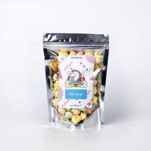 A pouch of popcorn on a white background. The popcorn is coloured different pastel shades and the pouch is labelled with a Unicorn logo and named Sweet Shop Mix