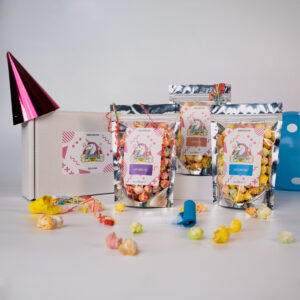 A display of 3 popcorn pouches and the gift box they come in. displayed with a party hat balloon and streamers