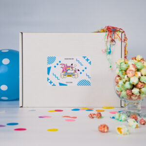 Front of Uniqucorn-tails gift box displayed with a balloon and some party poppers along side a glass of Cheeky V popcorn