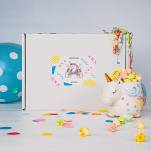 Front of Popcorn gift box which is a white box with a sticker on Saying Uniqucorn Collection. Displayed with a balloon confetti and some rainbow popcorn in a unicorn mug